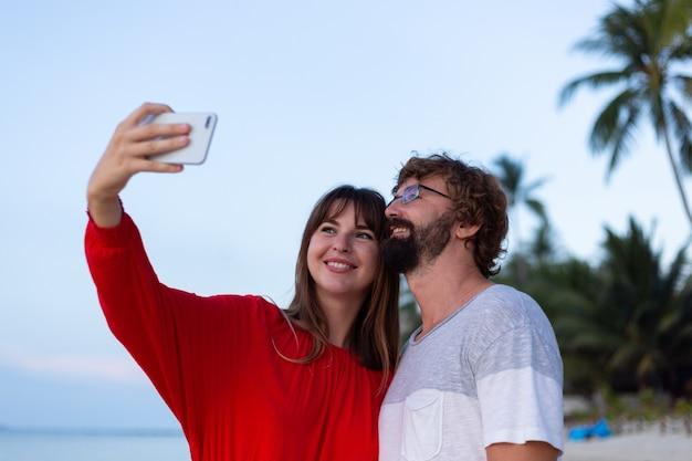 Couple romantique sur la plage au coucher du soleil
