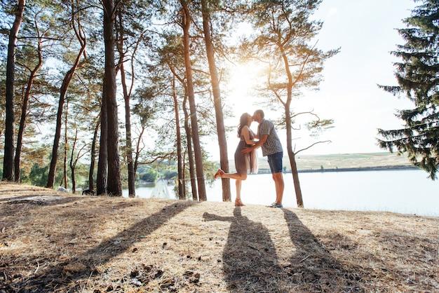 Couple romantique sur la plage au fond de coucher de soleil coloré