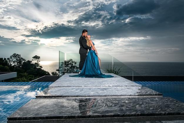 Couple romantique posant près de la piscine à débordement sur le fond d'un beau paysage marin et ciel nuageux. une fille dans une longue robe bleue et un homme dans un costume formel la serrent dans ses bras.