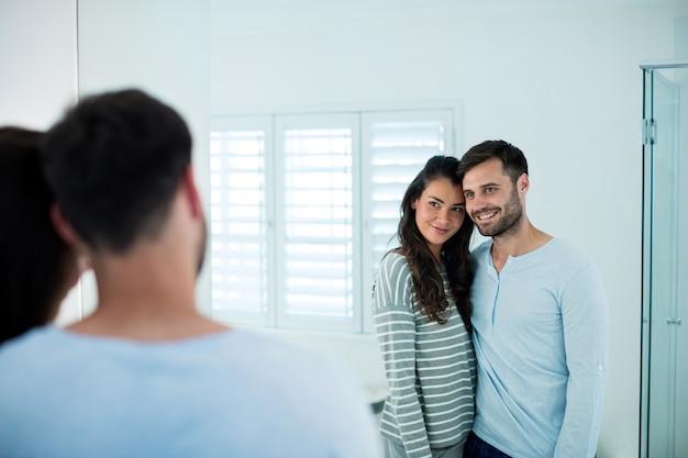 Couple romantique à la recherche de miroir de salle de bain ensemble