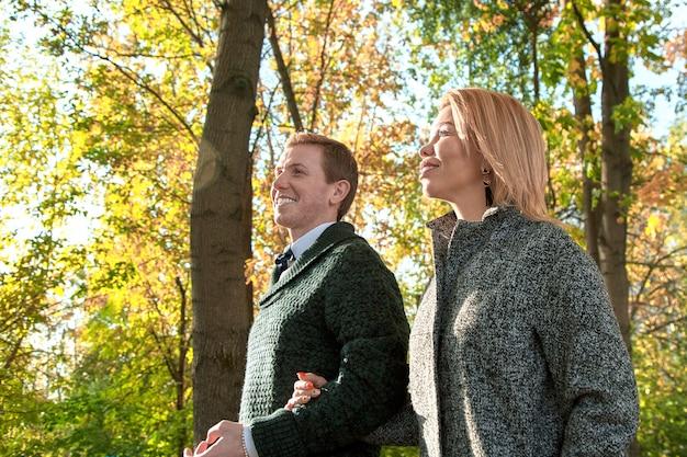 Couple romantique se détendre dans le parc en automne, câlins, baisers, profiter de l'air frais, de la belle nature, du beau temps d'automne. bien-aimé passer du temps ensemble