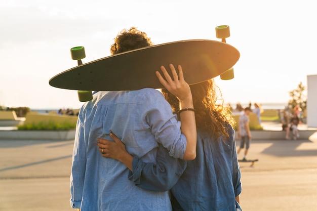 Un couple romantique de skateurs profite du coucher du soleil embrassant avec un longboard dans les mains dans un skate park urbain