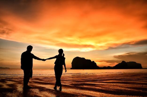 Couple romantique tenant la main au coucher de soleil sur la plage
