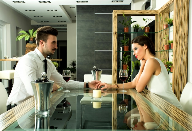 Un couple romantique avec un verre de vin dans la salle à manger
