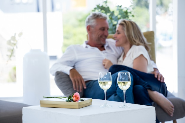 Couple romantique avec verres à vin blanc par rose et coffret cadeau sur table