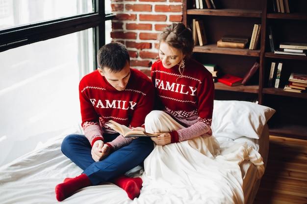 Couple, rouges, chandails, lecture, livre, lit, ensemble