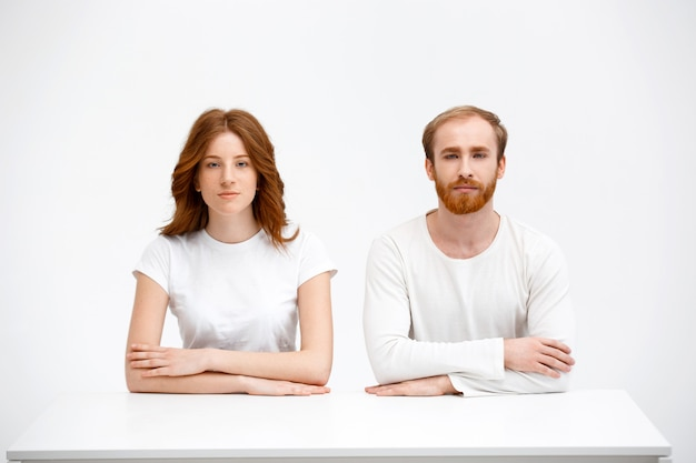 Couple rousse s'asseoir comme des étudiants sur le bureau