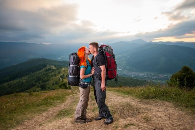 Couple de routards s'embrasse sur la route en montagne