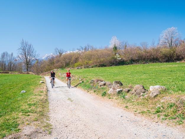 Couple s'amusant en faisant du vélo de montagne sur un chemin de terre en journée ensoleillée