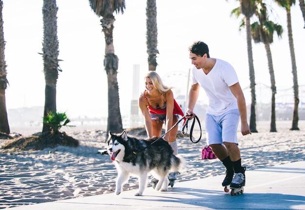 Couple s'amusant avec leurs patins à roulettes et husky ludique