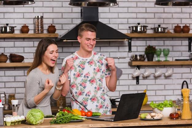 Couple s'amusant avec un ordinateur portable dans la cuisine