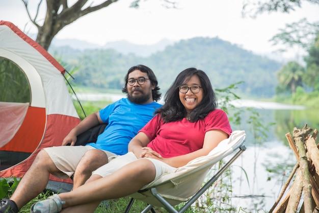Couple s'amusant à profiter de la nature en camping