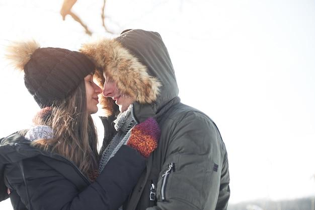Le couple s'amuse et rit. baiser. couple de jeunes hipster s'embrassant à winter park. histoire d'amour d'hiver, un beau jeune couple élégant. concept de mode d'hiver avec copain et copine