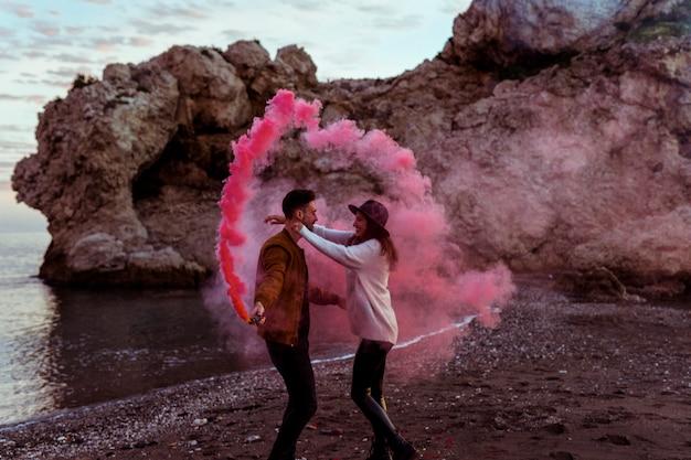 Couple s'amuser avec une bombe de fumée au bord de la mer