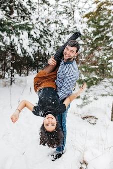 Couple s'amuser dans la forêt d'hiver