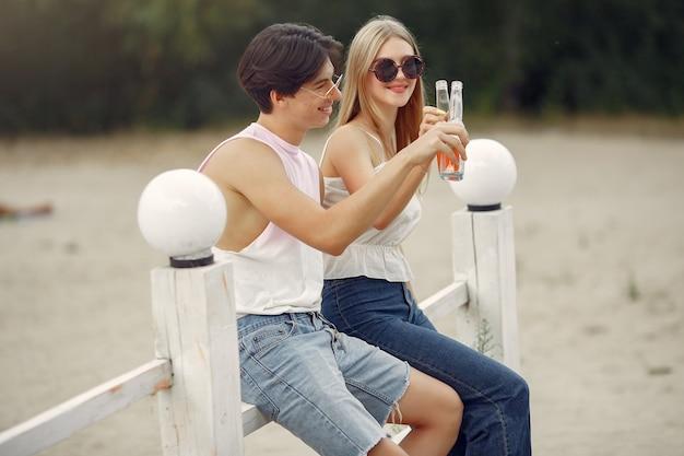 Couple s'amuser sur une plage avec des boissons