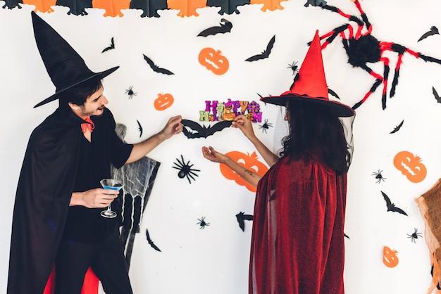 Couple s'amuser tenant des citrouilles et portant des costumes habillés de carnaval d'halloween
