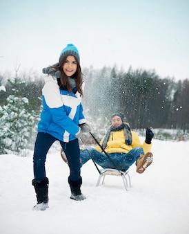 Couple s'amuser sur le traîneau en hiver