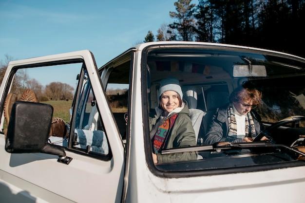 Couple s'arrêtant pour regarder une carte dans une camionnette