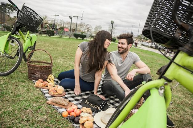 Couple, s'asseoir ensemble, dans parc, déguster