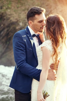 Couple s'embrassant au coucher du soleil, couple d'amoureux s'embrassant au coucher du soleil. cérémonie de mariage à l'extérieur. belle mariée et le marié avec bouquet de fleurs. robe de mariée blanche pour la mariée. câlin de couple de mariage d'amour. flou