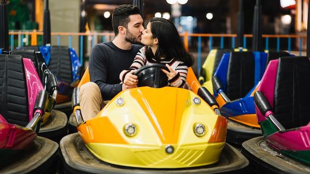 Couple s'embrassant dans les autos tamponneuses