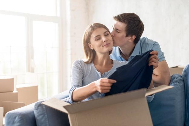 Couple s'embrassant en faisant ses valises pour sortir