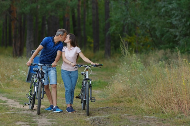 Couple s'embrassant en forêt, promenade romantique à vélo