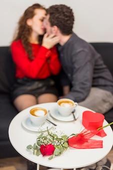 Couple s'embrassant près de la table avec des tasses de rose et de café