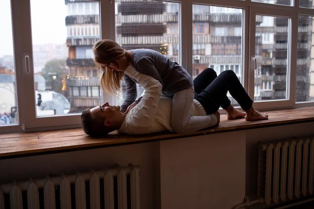 Couple s'embrassant et s'amusant dans leur chambre près de la fenêtre, un mec tenant sa belle fille bien-aimée dans ses bras