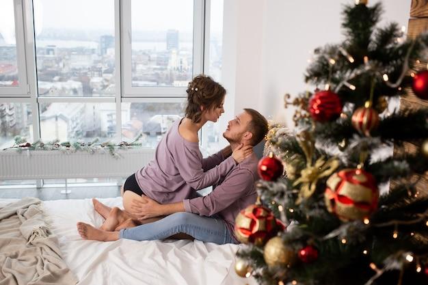 Couple s'embrassant et s'embrassant à la maison le temps de noël