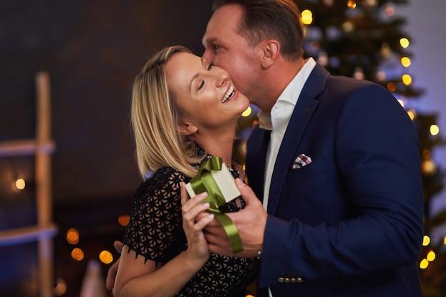 Un couple s'embrasse devant un arbre de noël tenant un cadeau. photo de haute qualité