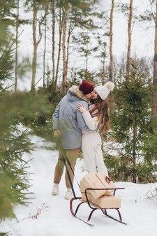 Un couple s'embrasse et s'embrasse dans une forêt de conifères d'hiver et porte des boîtes avec des cadeaux sur un traîneau