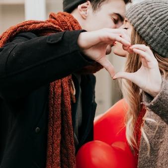 Couple s'embrasser et faire un geste de coeur