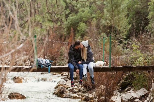 Couple avec sac à dos assis sur le pont