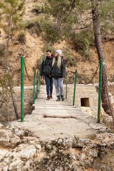 Couple avec sac à dos marchant sur le pont