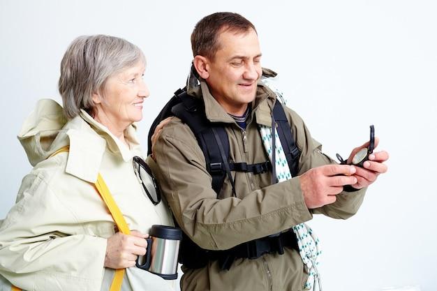 Couple avec sacs à dos en regardant la boussole
