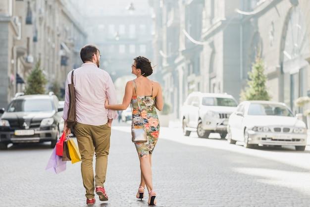 Couple avec des sacs à provisions marchant sur la rue