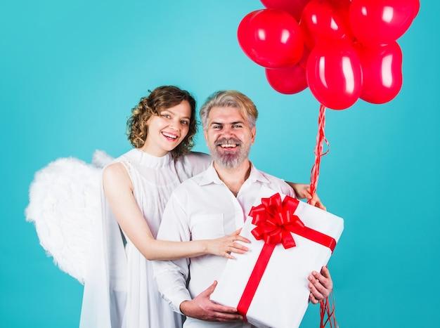Couple à la saint-valentin avec des ballons de coeur et des cadeaux. anges de la famille. cadeaux de la saint-valentin.