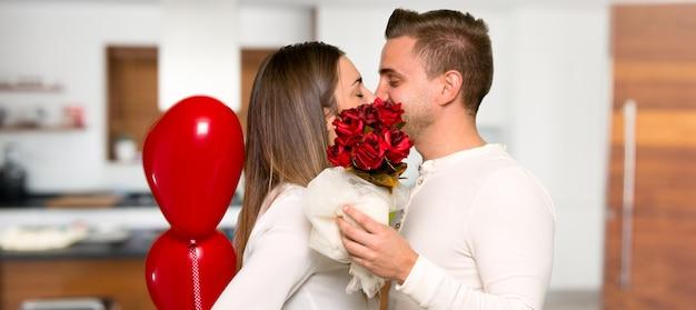 Couple en saint valentin avec des fleurs et des ballons en forme de coeur dans une maison