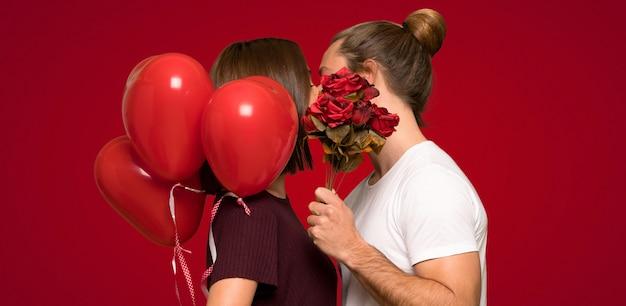 Couple à la saint-valentin avec des fleurs et des ballons en forme de cœur sur fond rouge