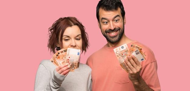 Couple en saint valentin prenant beaucoup d'argent sur fond rose isolé