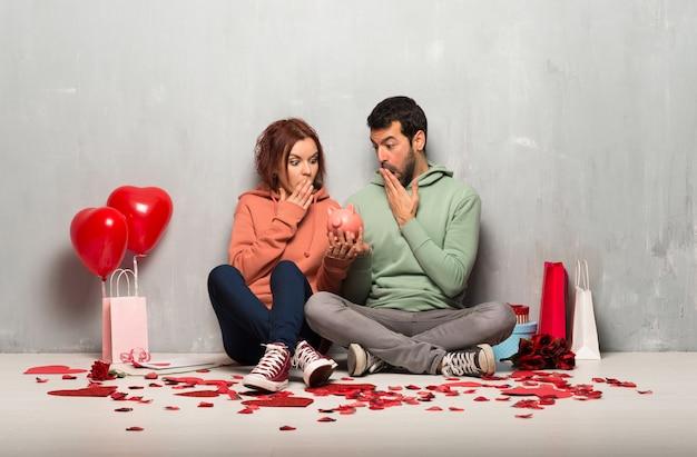 Couple en saint valentin surpris tout en tenant une tirelire