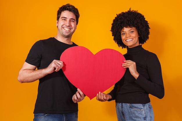 Couple de la saint-valentin tenant un coeur en papier. concept de la saint valentin
