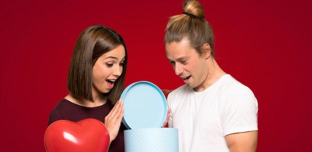 Couple à la saint-valentin tenant sa boîte cadeau en mains sur fond rouge