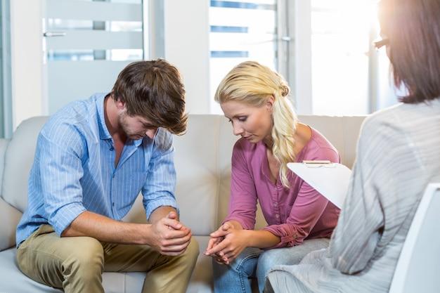 Couple sans sourire parlant avec leur thérapeute