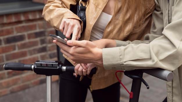 Couple avec scooters électriques et smartphone à l'extérieur