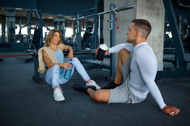 Un couple se détend sur le sol après un entraînement de fitness en salle de sport