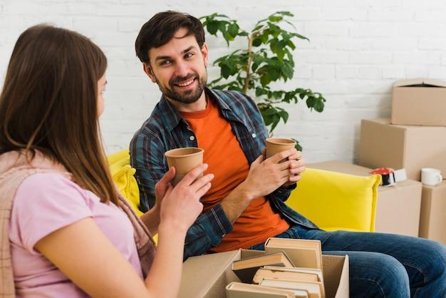 Couple se détendre sur le canapé avec une boisson chaude dans la nouvelle maison