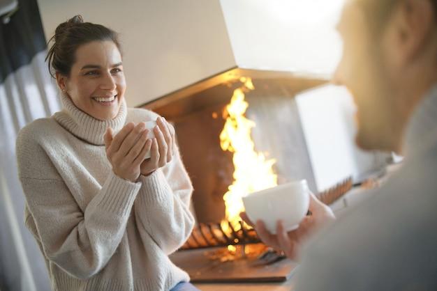 Couple se réchauffant près du feu avec des boissons chaudes